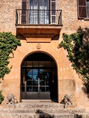 Puerta de acceso principal elevada sobre seis escalones, con arco de medio en cuya clave se encuentra un medallón con el Corazón de Jesús y un serafín. El umbral de la puerta está flanqueado por leones yacentes.