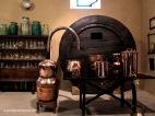 Bodega, zona de preparación y destilados espirituosos con una gran barrica de roble viejo, una estantería con porrones y otros objetos de vidrio, un bonito alambique y diversas ollas de cobre pulido.