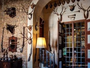 Sala de caza con trofeos, escopetas, cuernas y algunas antiguas granadas de cañón. La reja da paso a la biblioteca y sala de estudio de la casa.
