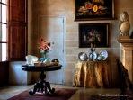 Rincón del comedor con decoración floral y cuadros de bodegones de frutas y dulces.