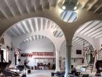 Granero o cuartera, con cubierta sostenida por arcos asimétricos con óculos en su tímpano, que se apoyan en las paredes laterales y en unos esbeltos pilares ochavados que parten en dos el vano.