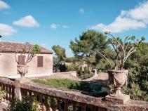 Terraza con barandilla de balaustres e hidrias decorativas.