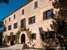 Fachada principal de Es Calderers con la puerta sobreelevada y dos leones yacentes protegiendo la entrada.