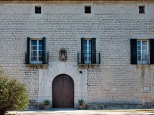 Puerta blasonada de acceso principal a Sollerich y detalle parcial de su fachada de mampostería careada con piezas regulares colocadas a matajunta. Sobre la clave del arco se aprecia el Escudo de Armas de los Marqueses de Sollerich.