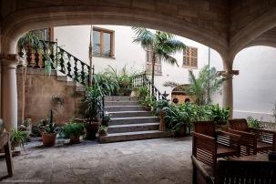 Galería cubierta con arcos carpaneles sobre columnas de fuste liso abombado y patio de acceso a una vivienda.