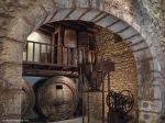 Detalle parcial del interior de una bodega tradicional ya en desuso en Biniagual, en primer término se aprecia una prensa mecánica de uva.